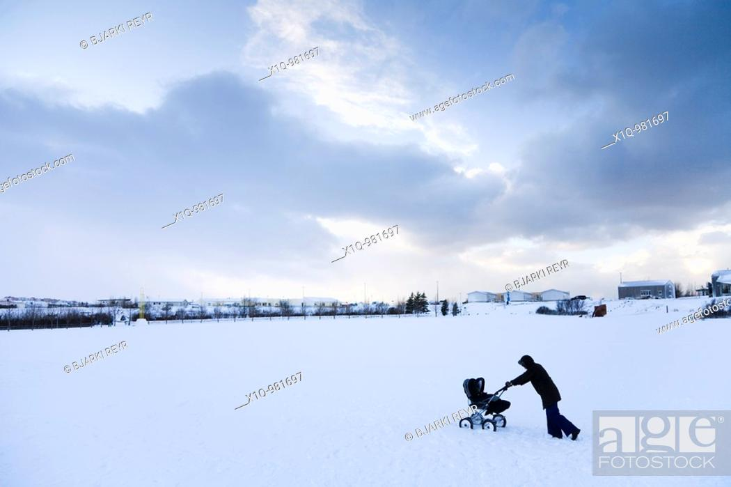 Stock Photo: A woman walking with a pram in the snow  Hafnarfjordur, Iceland.