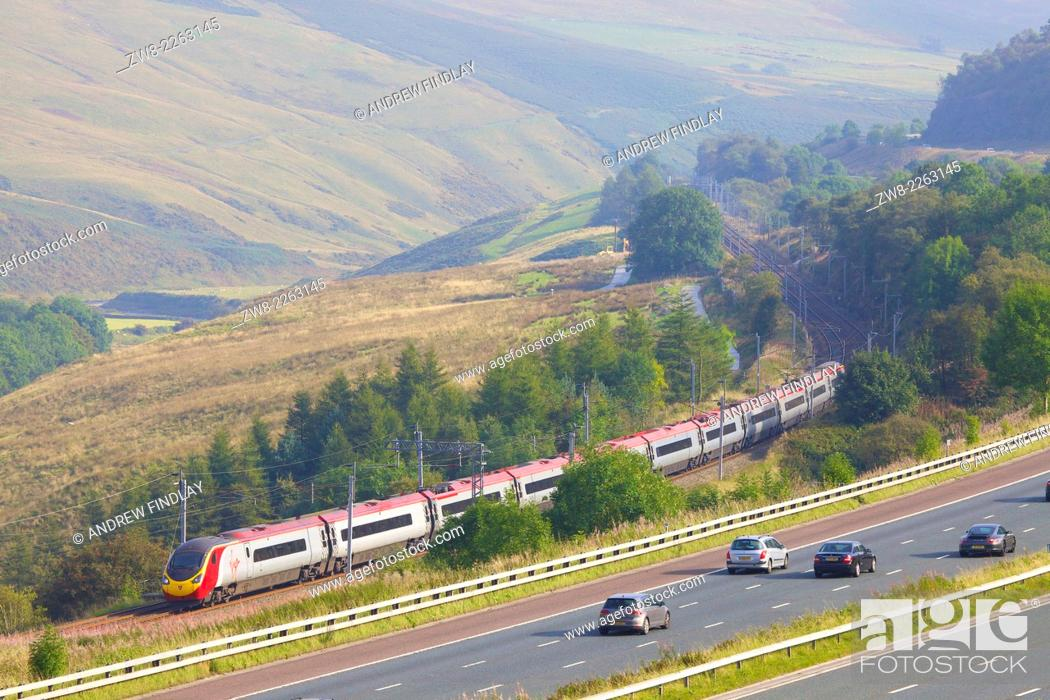 Stock Photo: Class 390 Pendolino Virgin train passing the M6 motorway in the River Lune Valley. Howgills, Cumbria, West Coast Main Line, England, UK.