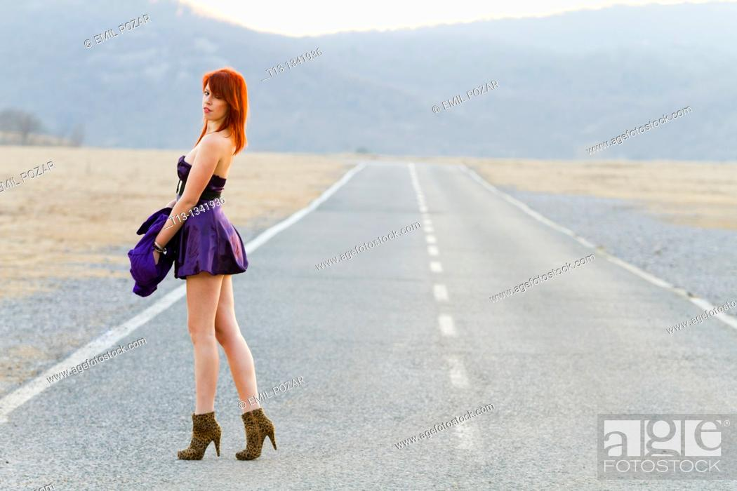 Stock Photo: Walking on the road in a very seductive clothing young woman.