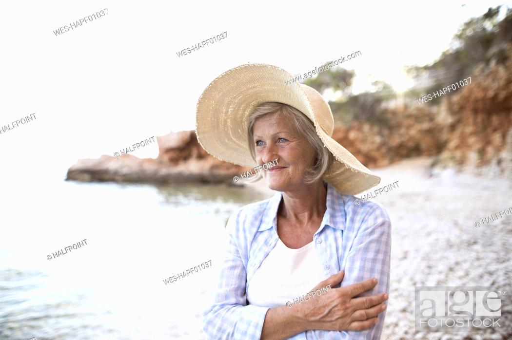 Stock Photo: Portrait of happy mature woman wearing straw hat on the beach.
