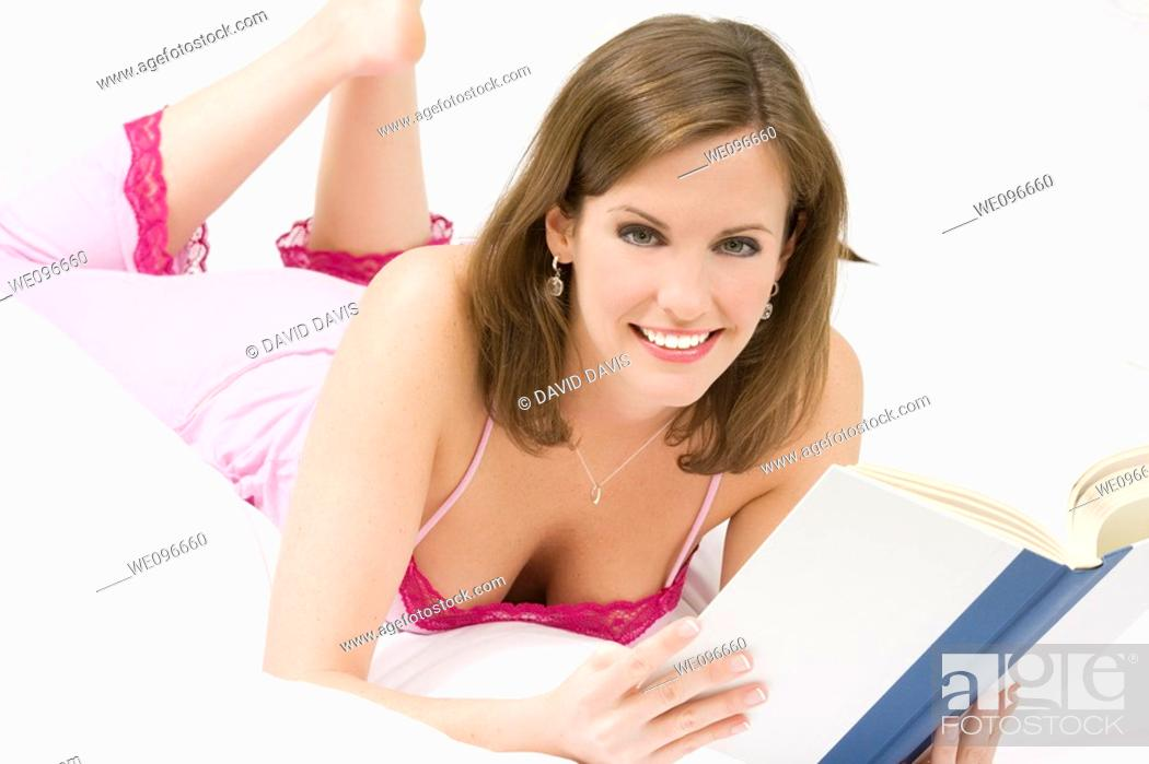 Stock Photo: Beautiful Caucasian woman in bed reading a book.