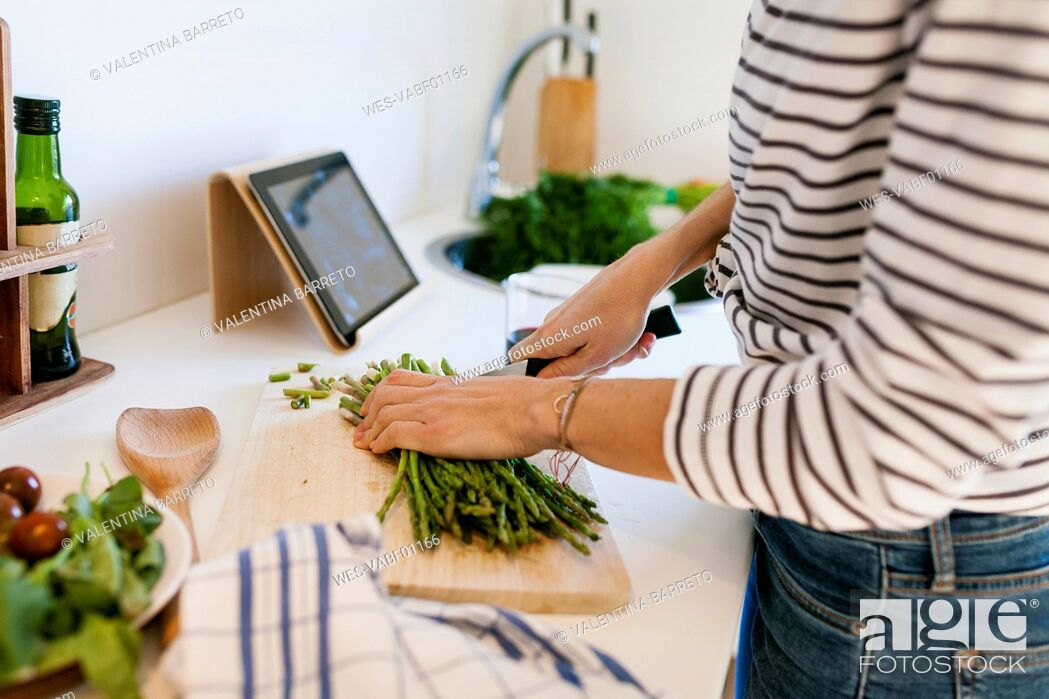 Stock Photo: Young woman cooking at home using digital tablet for recipe.