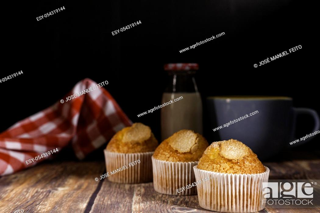 Stock Photo: three delicious cupcakes, milk bottle, blue ceramic cup and napkin on wooden table on black background.