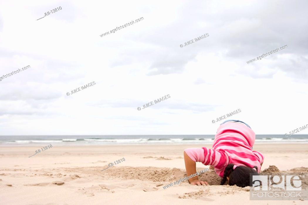 Stock Photo: Girl 5-7 digging hole on beach.