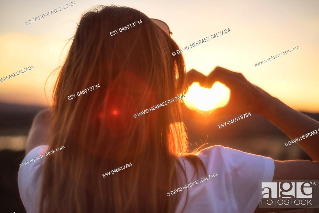 Stock Photo: Love sign. Woman making heart with her hands at sunset.