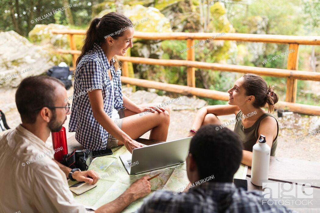 Stock Photo: Group of hikers sitting together planning a hiking route using map and laptop.