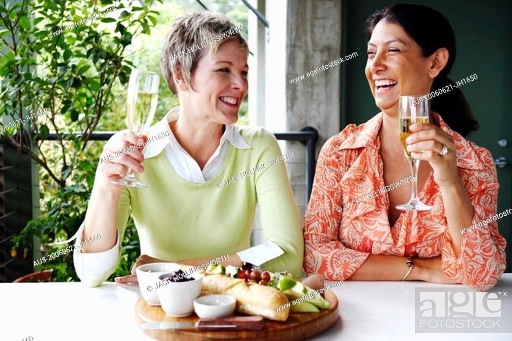Stock Photo: Close-up of two mature women holding champagne flutes and smiling.