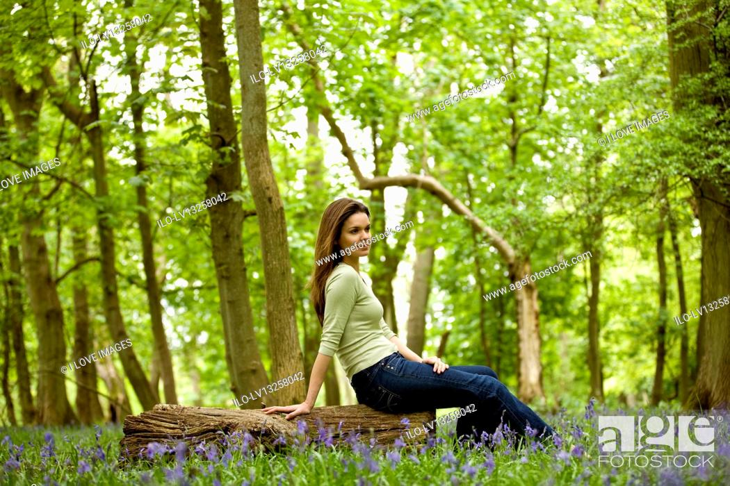 Stock Photo: A young woman sitting on a log, resting.