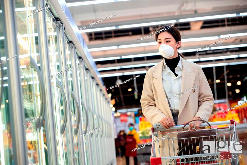Stock Photo: Wearing a mask of young women shopping in the supermarket.