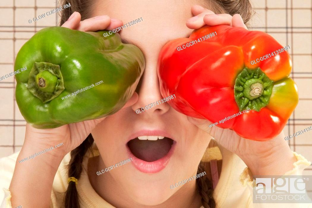 Stock Photo: Close-up of a girl holding bell peppers over her eyes.