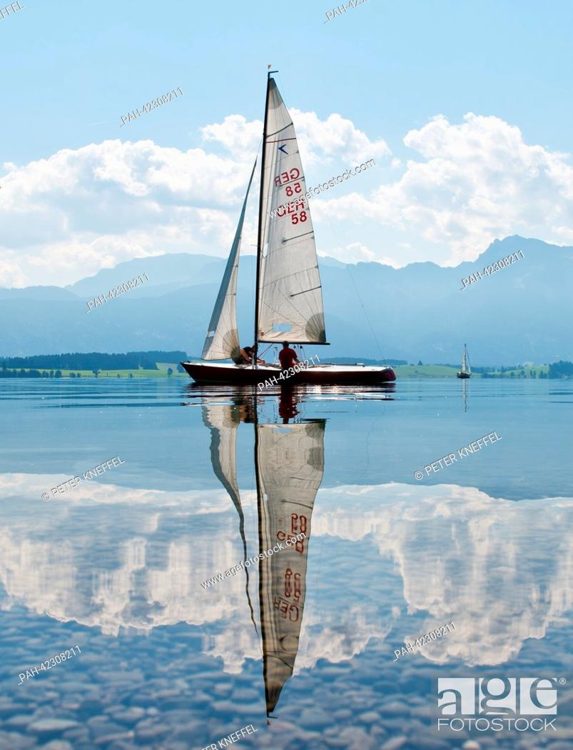 Stock Photo: A sailing boat sails on the calm water of the Forggensee lake with the panoramic view of the alpine mountains reflecting on the water surface near Dietringen.