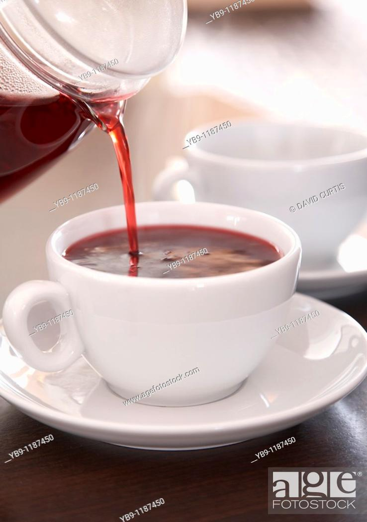 Stock Photo: Herbal tea being poured into a cup.