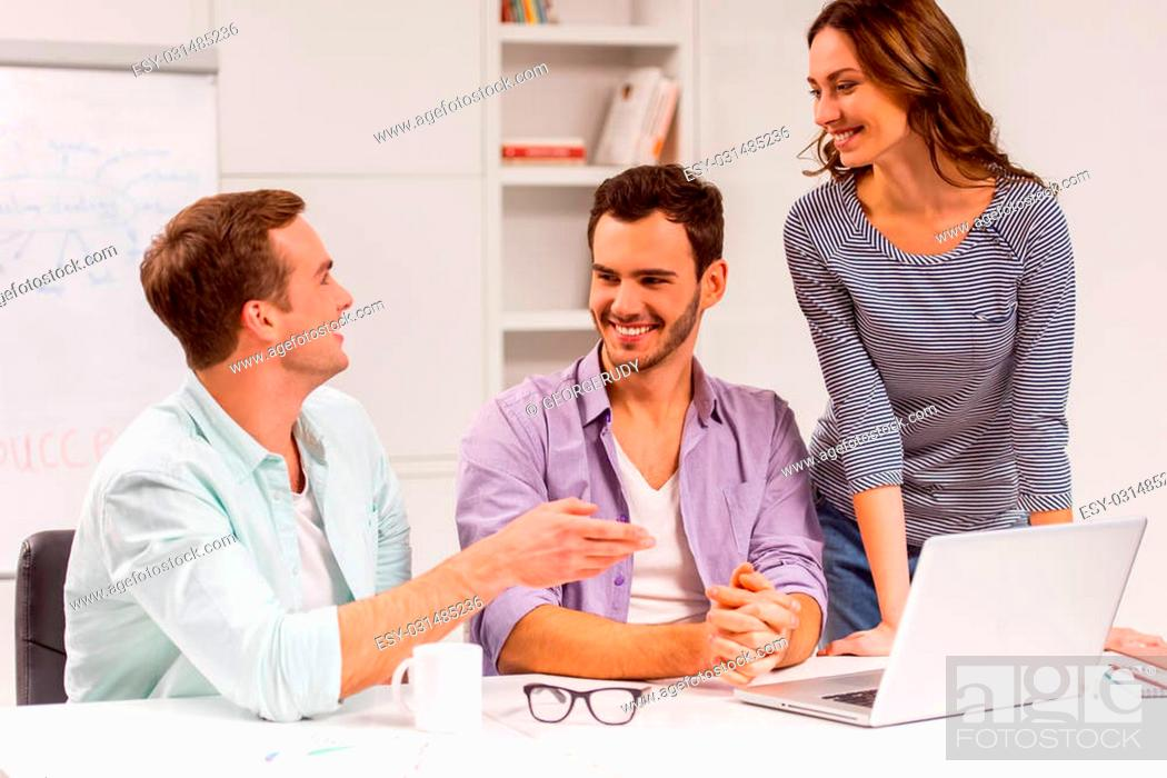 Photo de stock: Two young attractive businessmen and one beautiful businesswoman in casual clothes using laptop, smiling and talking while working in office.