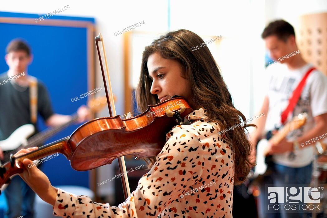 Imagen: Young female college student playing violin in recording studio.