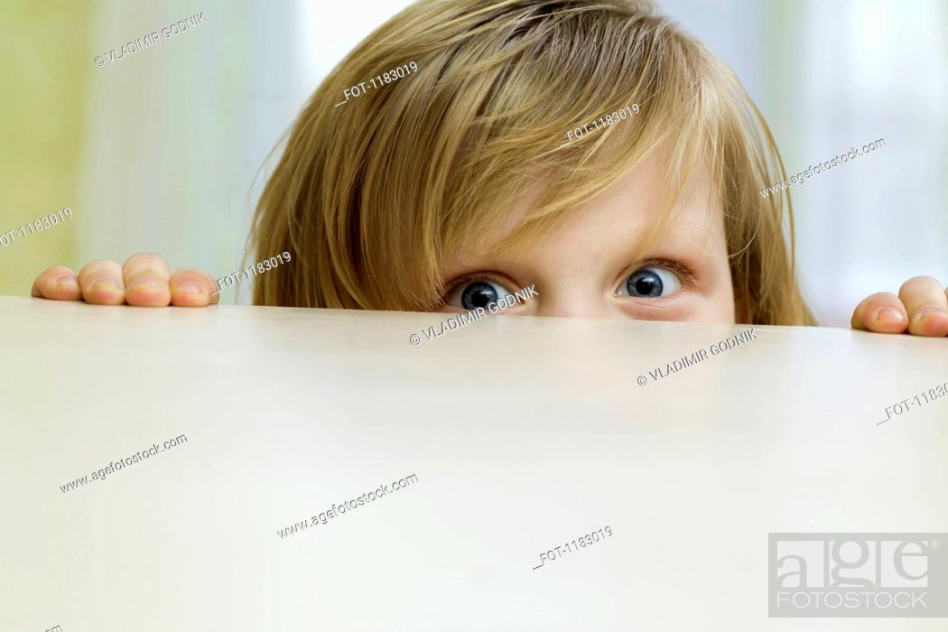 Stock Photo: A mischievous girl peeking over the top of a table.