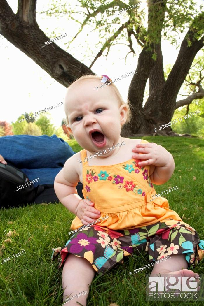 Stock Photo: A girl, 7 months old, yawning and sitting in the grass at a park.