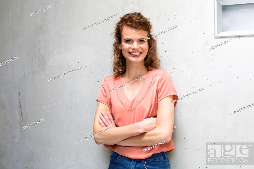 Stock Photo: Portrait of smiling woman leaning against concrete wall.