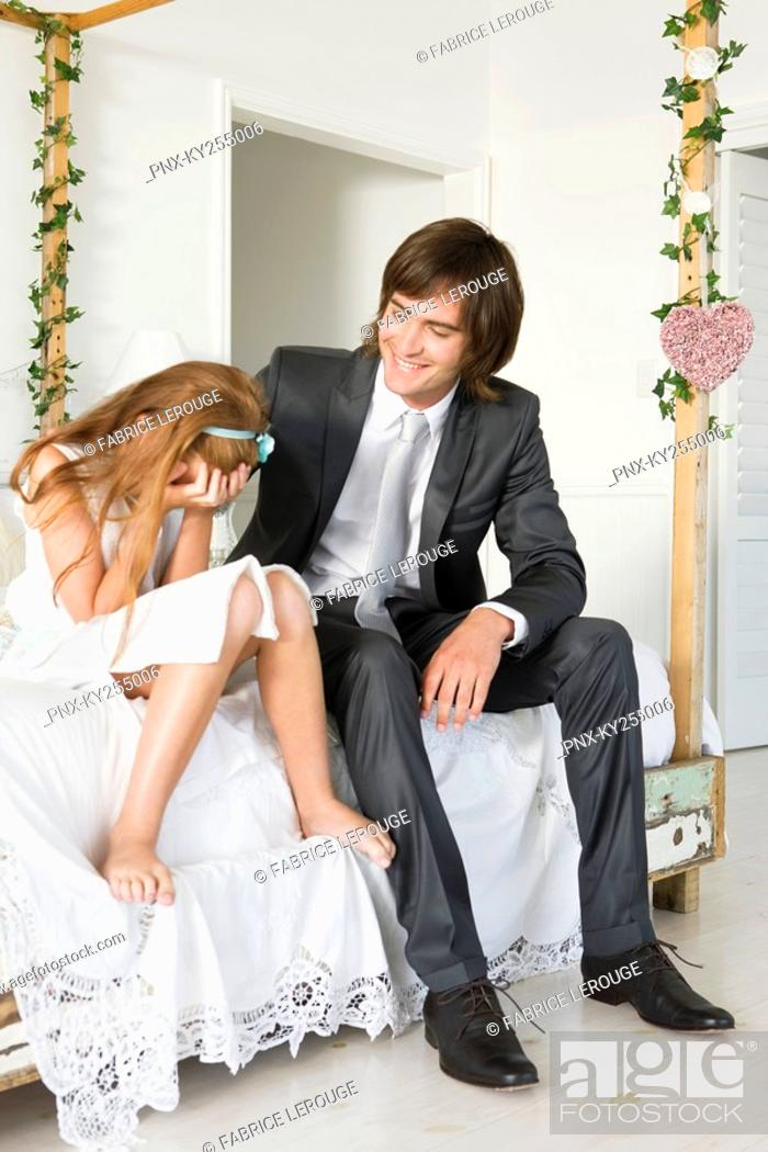 Stock Photo: Groom consoling a desperate girl sitting on the bed covering her face.