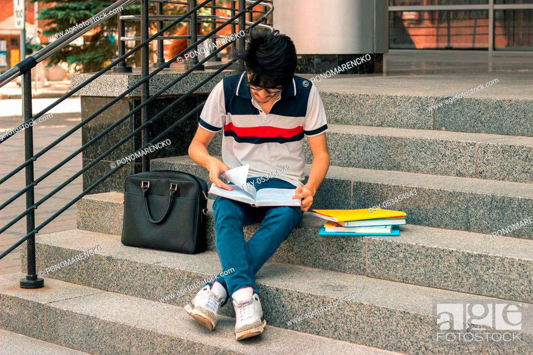 Stock Photo: young fashion guy reads books sitting on the street.