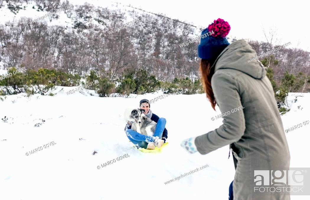 Stock Photo: Man and woman having funwith sled and dog in the snow.