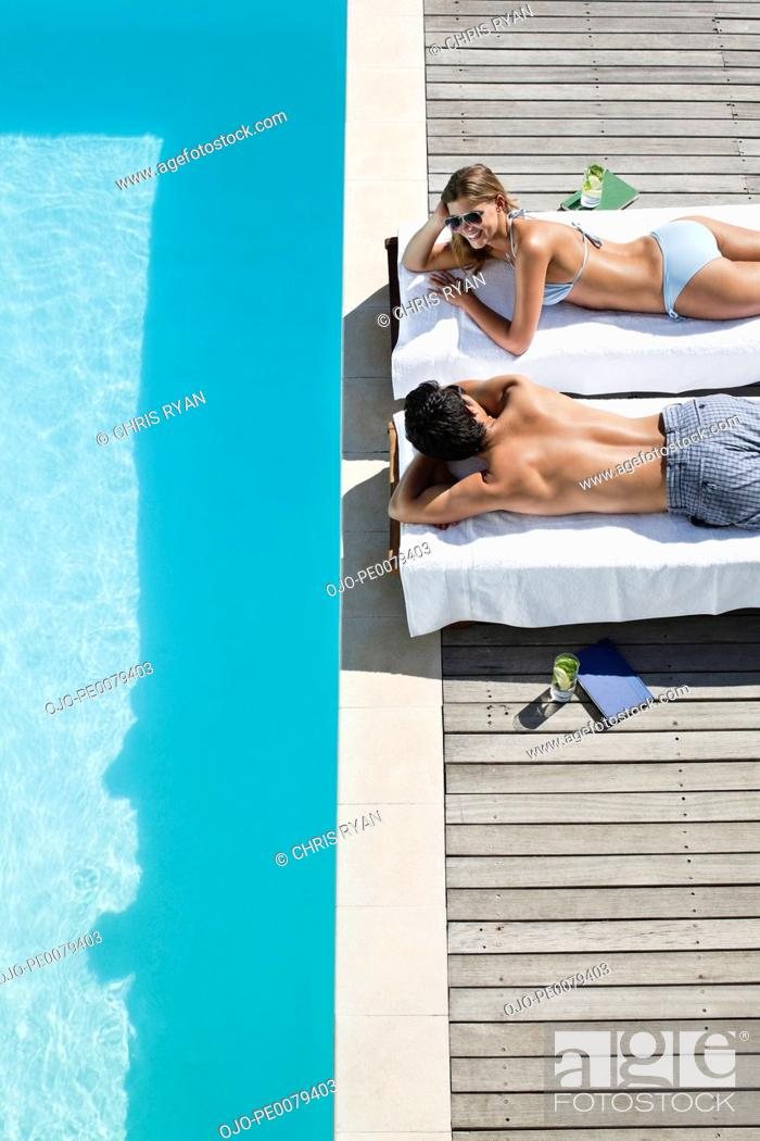 Stock Photo: Couple laying on lounge chairs near swimming pool.