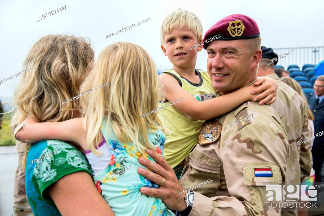 Stock Photo: Eindhoven Airbase, Eindhoven, Netherlands. Airforce military employee welcomed home by his wife and two children after being deployed to Afghanistan for six.