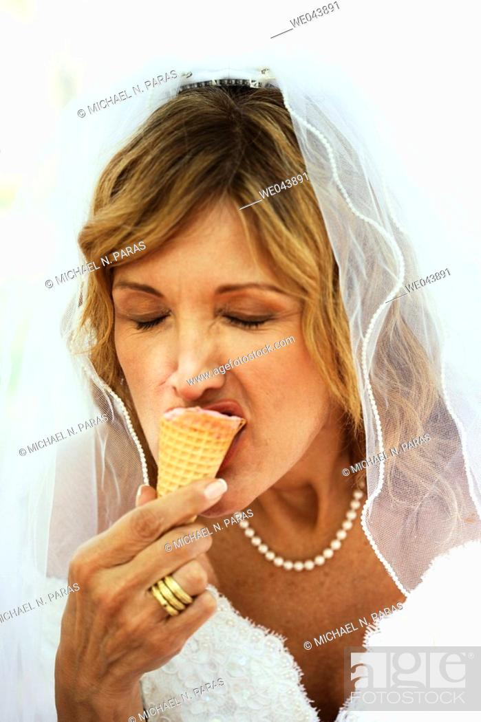Stock Photo: Bride eating ice cream cone with eyes closed.