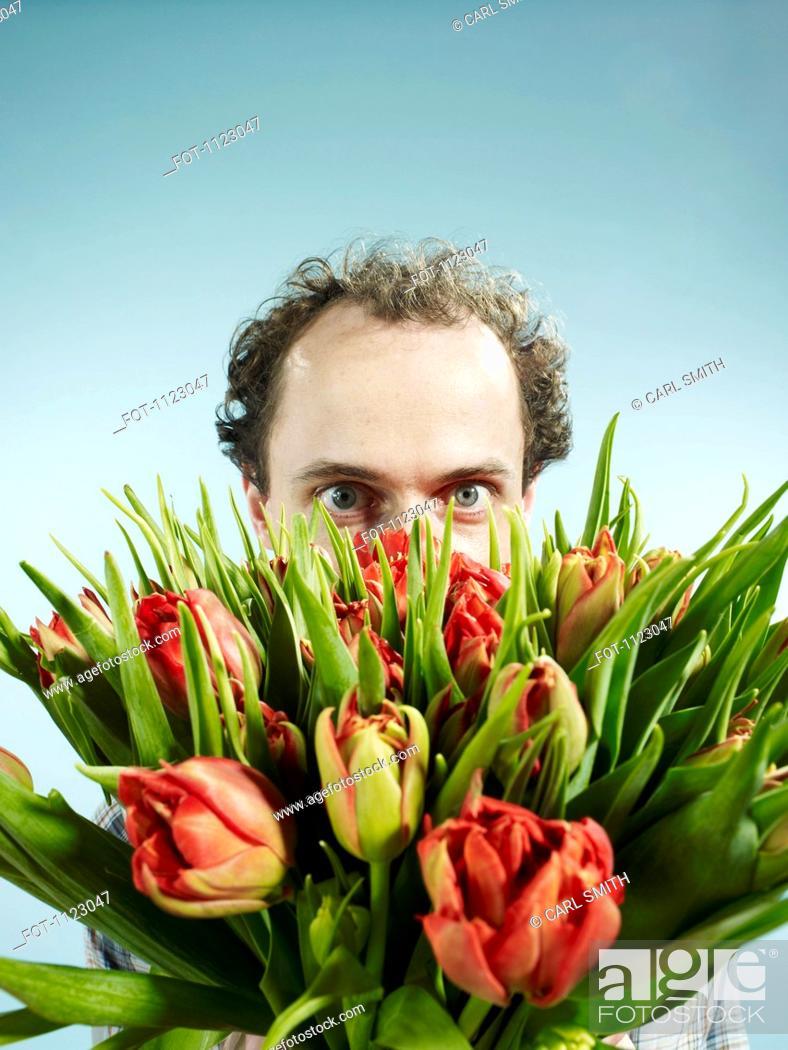 Stock Photo: A man nervously hiding behind a bouquet of tulips.