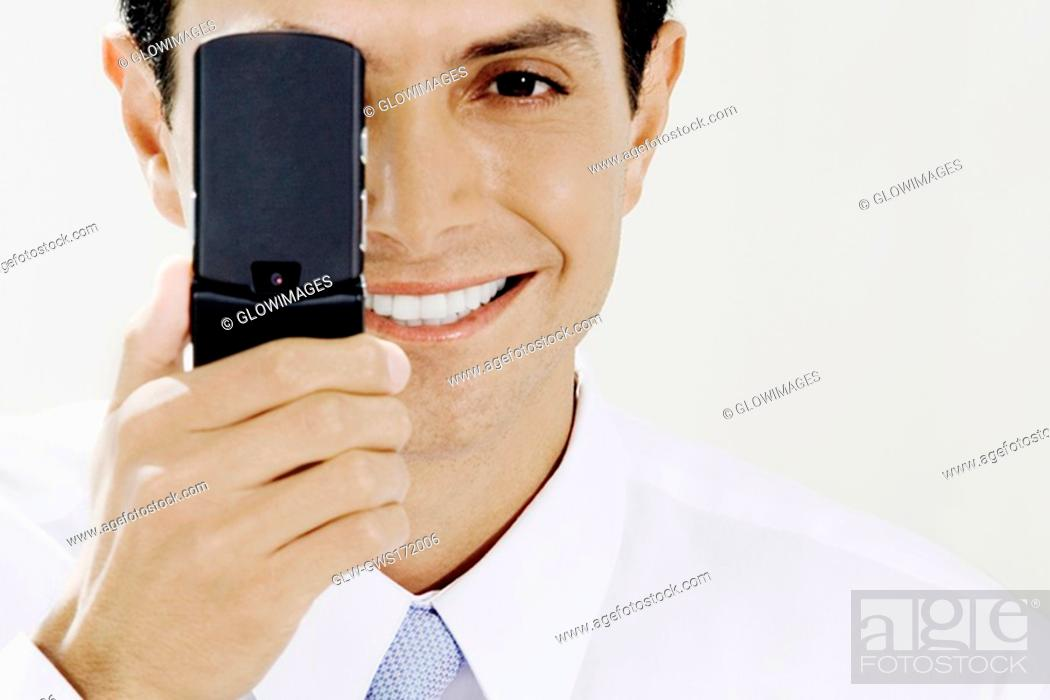 Stock Photo: Portrait of a businessman covering his eye with a mobile phone.