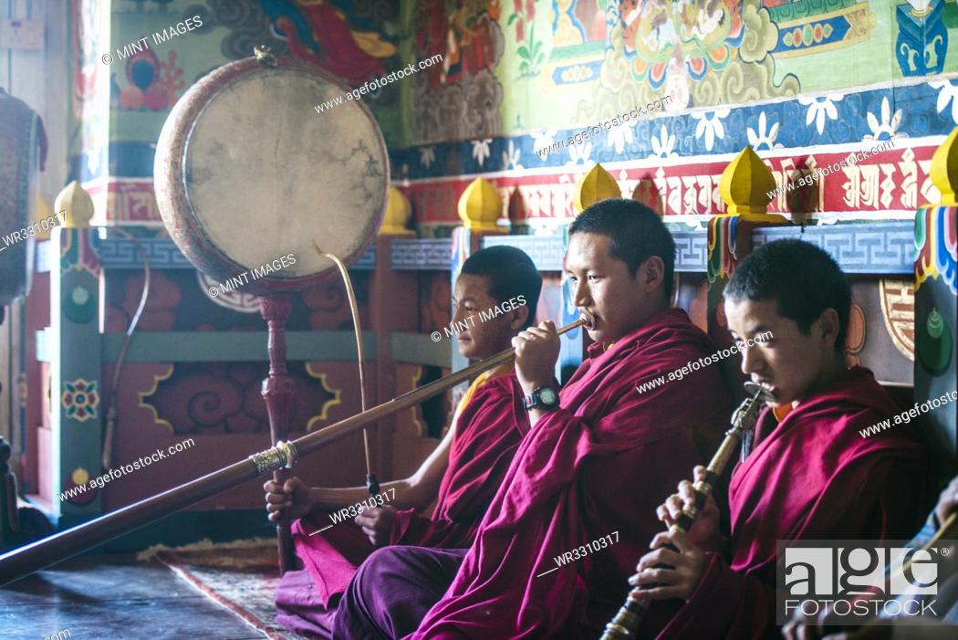 Imagen: Asian monks playing instruments on temple floor.