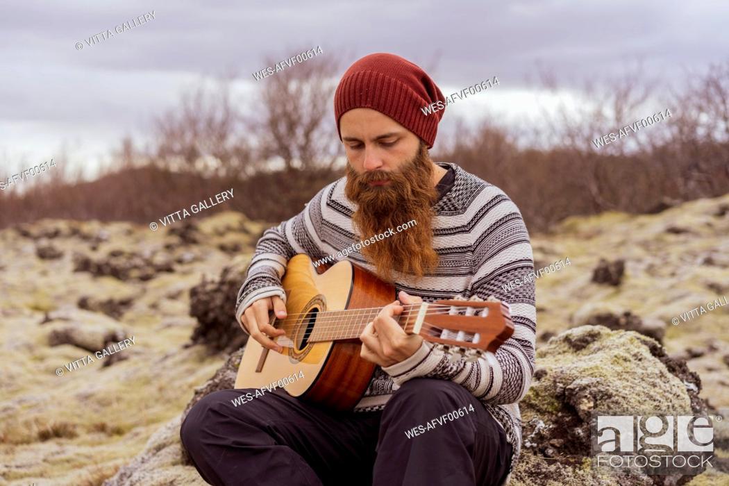 Imagen: Man sitting in wilderness, playing the guitar.