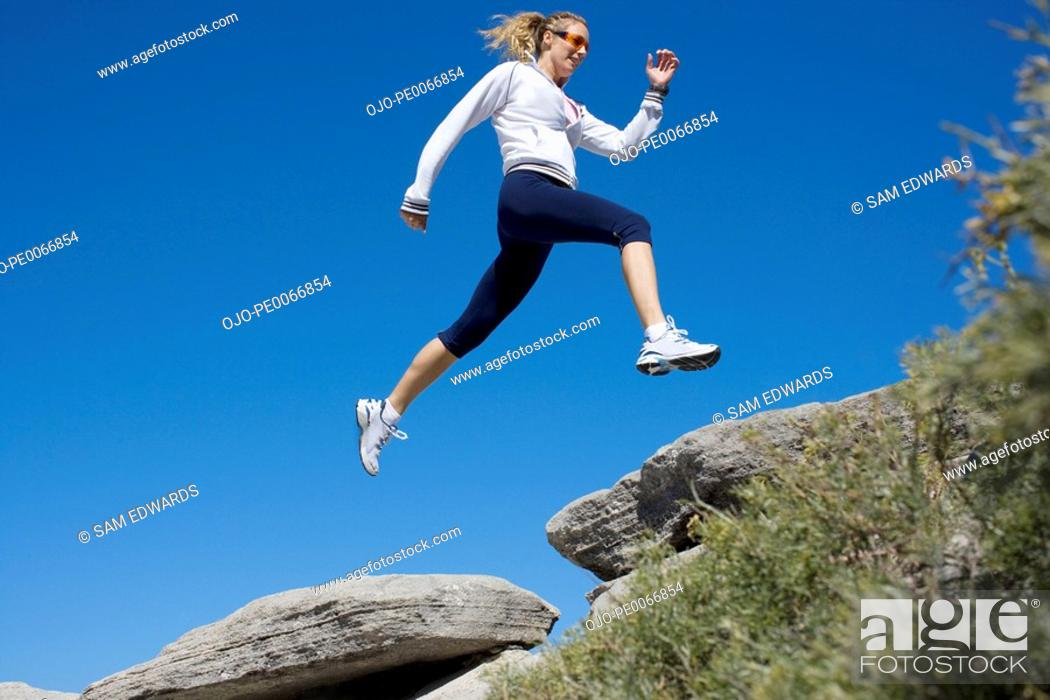 Stock Photo: Woman running over rocks.