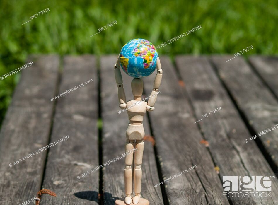 Stock Photo: A wooden mannequin with a world ball in his arms. Ecology concept, globalization.