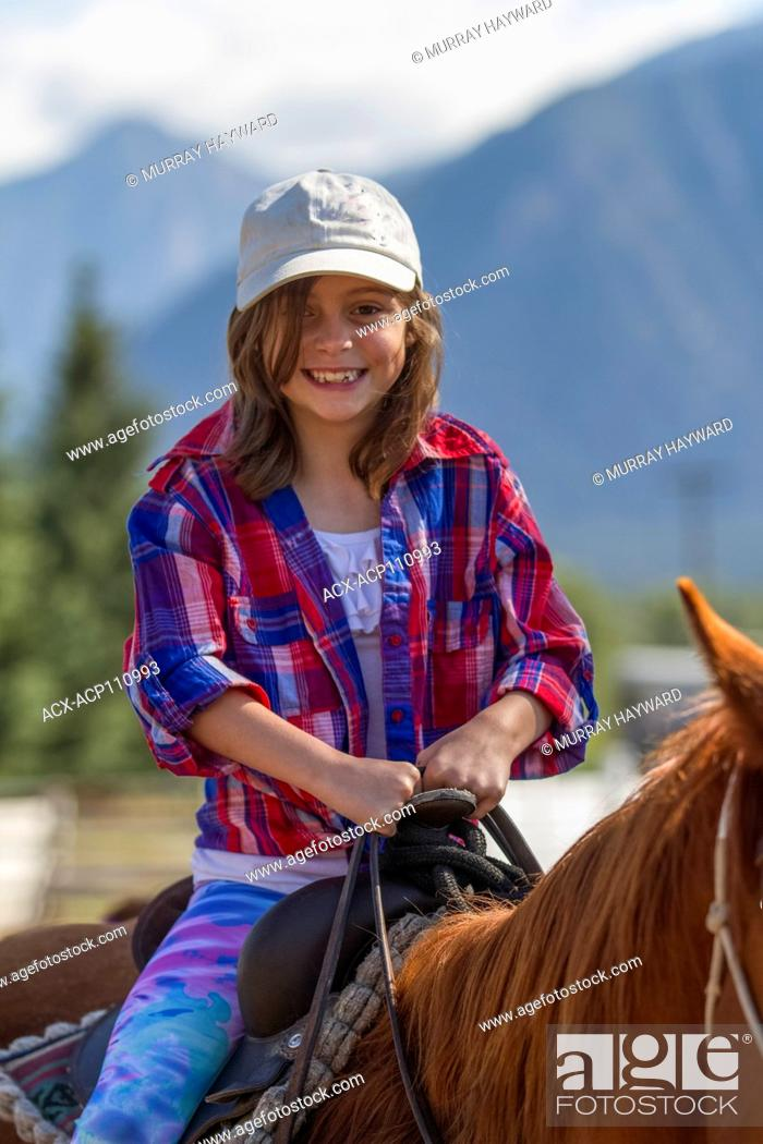 Imagen: Attractive, young girl, sitting in the saddle, on a trail ride adventure. Looking at camera. Cranbrook, BC, Canada.