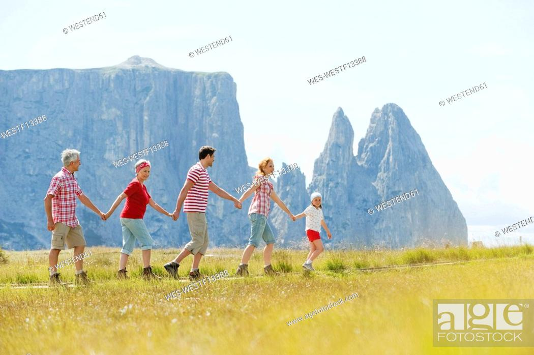 Stock Photo: Italy, Seiseralm, Family walking in field.