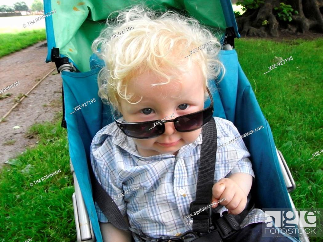 Stock Photo: 18 month boy sitting in pram wearing adult sunglasses, comical.