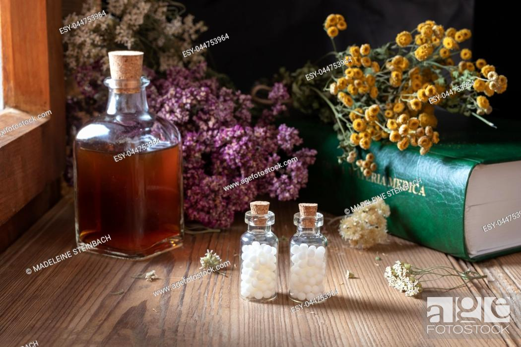 Stock Photo: Two bottles of homeopathic globules with dried herbs and a materia medica, i. e. a list of remedies and their therapeutic properties.