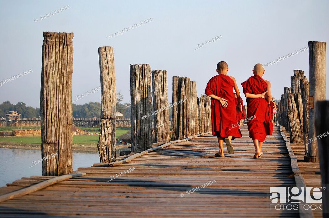 Stock Photo: Two young monks crossing U Bein bridge. Myanmar, Mandalay, Amarapura, U Bein.