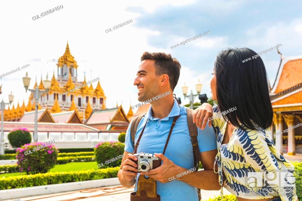 Stock Photo: Young tourist couple visiting temple, Bangkok, Thailand.