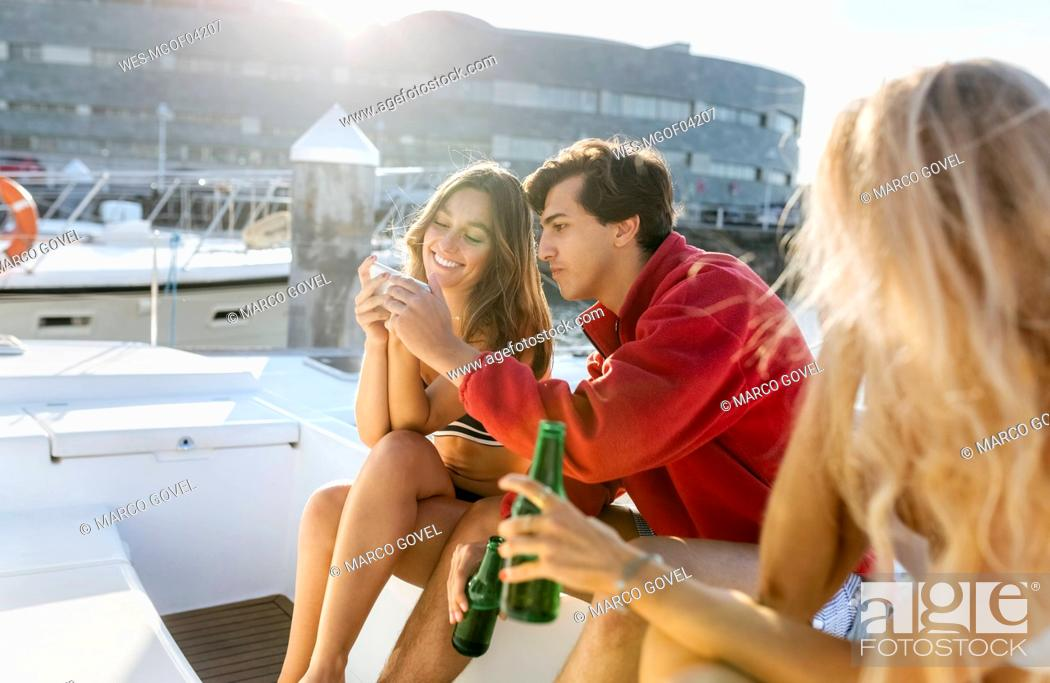 Stock Photo: Three young friends enjoying a summer day on a sailboat and using smartphone.