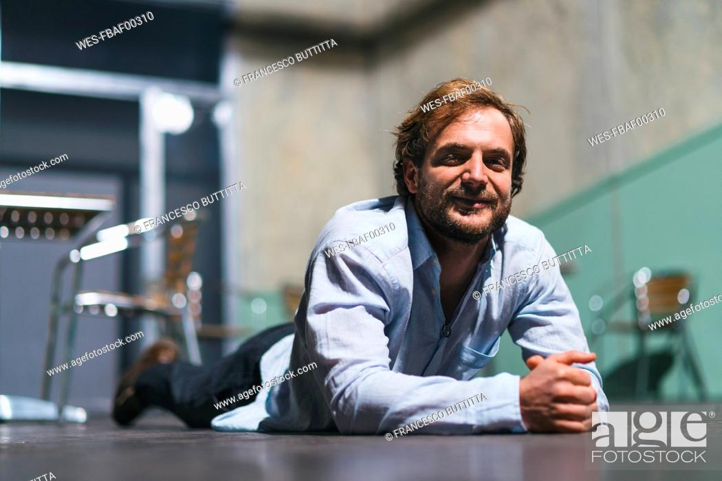 Stock Photo: Portrait of smiling actor lying on theatre stage.