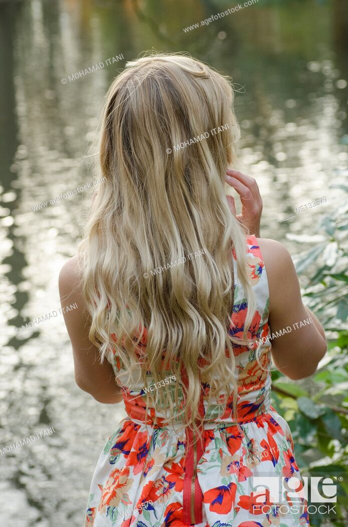 Stock Photo: Young blond woman standing by the lake.