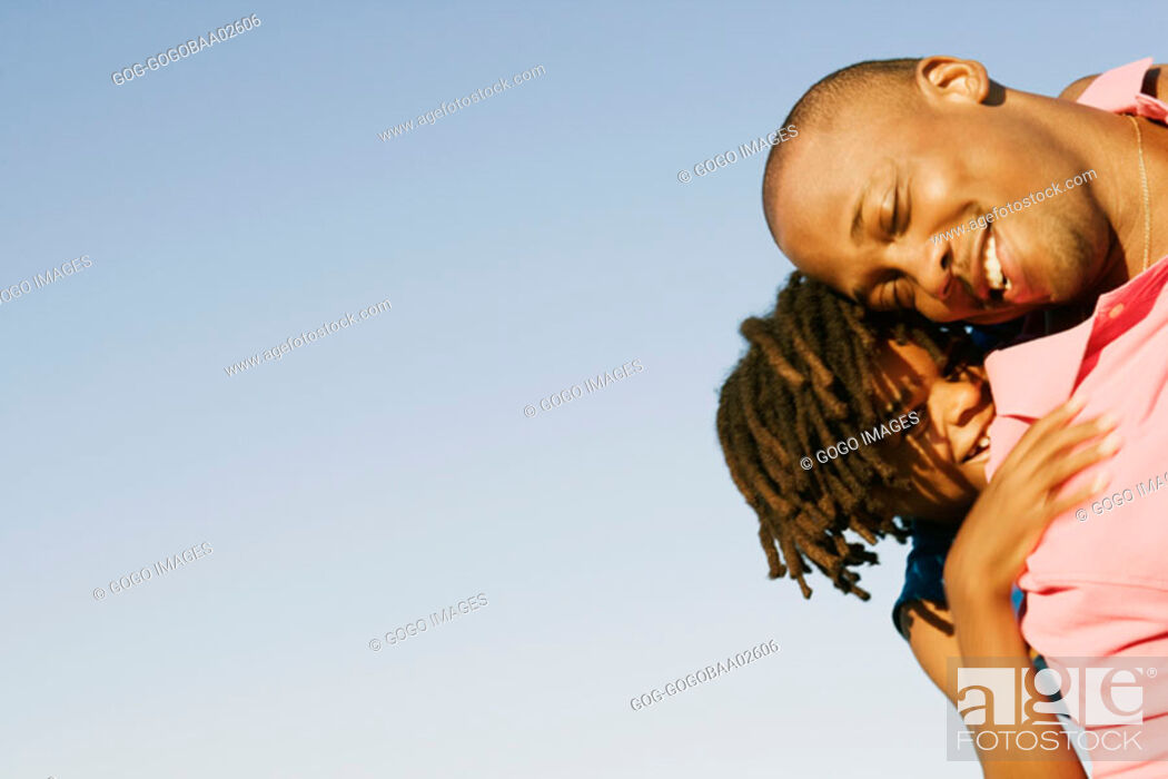 Stock Photo: African father carrying his daughter on his shoulders.