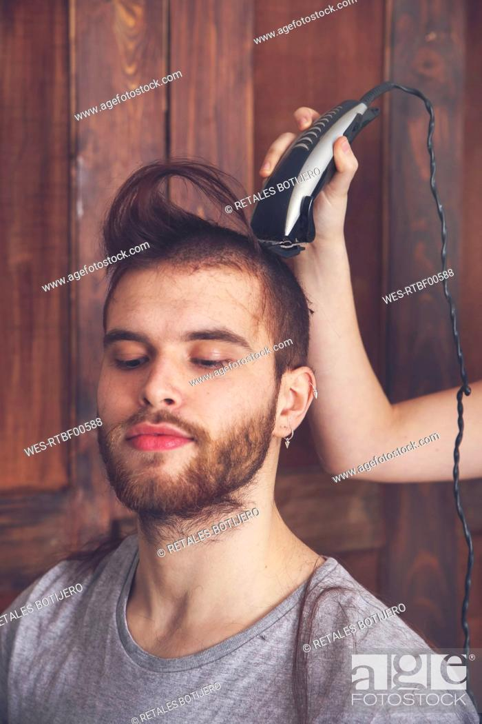 Portrait Of Young Man Getting A Haircut By His Girlfriend With Hair