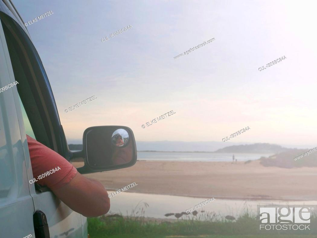 Stock Photo: Senior man sitting in car, looking at coastal view, Broulee, New South Wales, Australia.