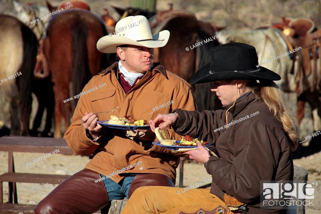 Stock Photo: Cowboy and cowgirl with hats having breakfast outside with horses in background in Saguaro National Park.