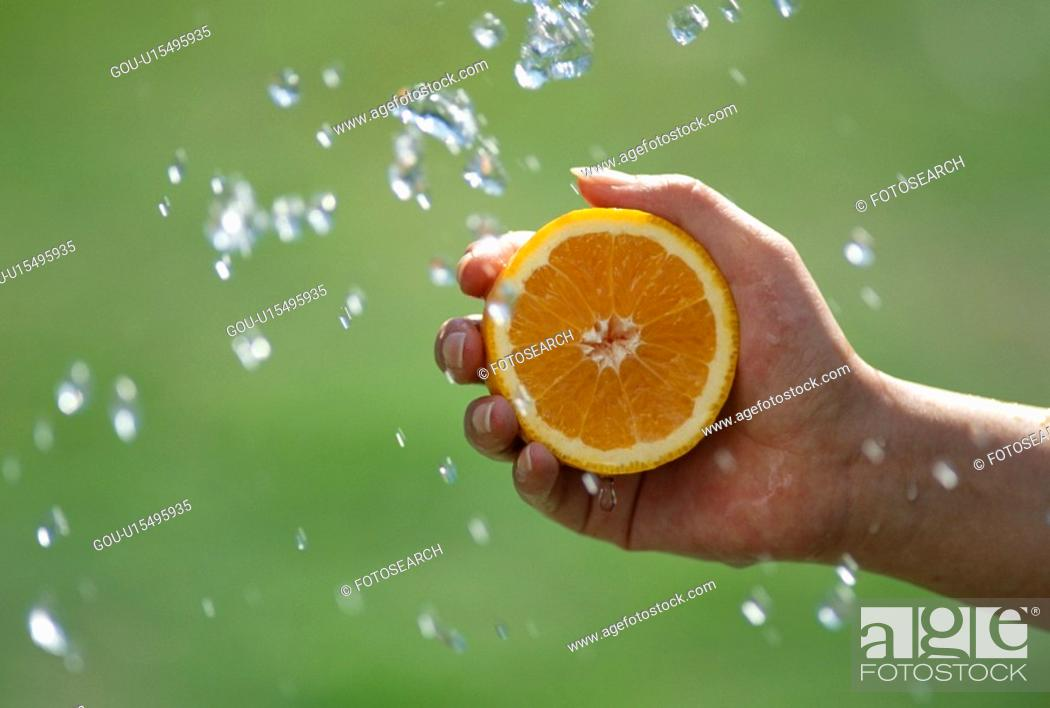 Stock Photo: A Hand With An Orange, And A Spray.