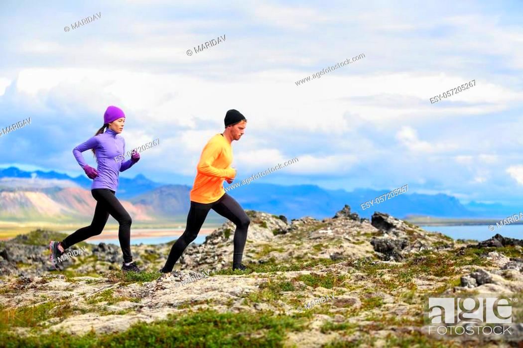 Imagen: Running people trail runners in cross country run. Woman and man runners training jogging outdoors in beautiful mountain nature landscape on Snaefellsnes.