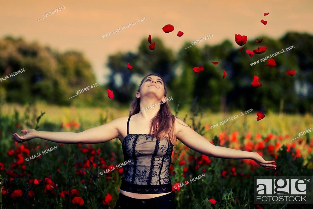 Stock Photo: Young woman playing with poppies in a poppy field, Croatia, Europe.