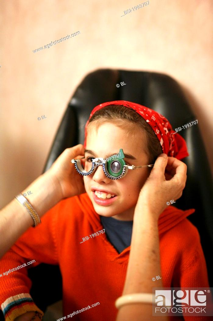 Stock Photo: OPHTHALMOLOGY, CHILD Photo essay in doctor's office. Follow-up visit at the ophthalmologist. 8-year-old boy. Test of visual acuity with trial frame.